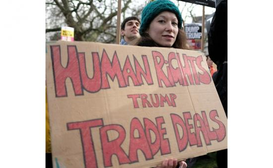 Woman with banner saying 'human rights trump trade deals'