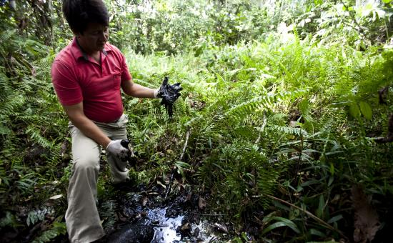 Man shows the crude oil abandoned by Texaco which contaminates the Ecuadorian Amazon