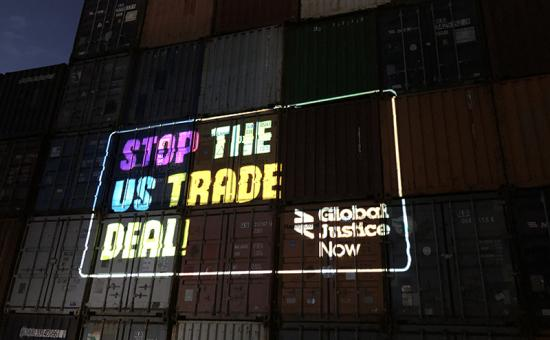 Projection of 'Stop the US trade deal' onto shipping containers